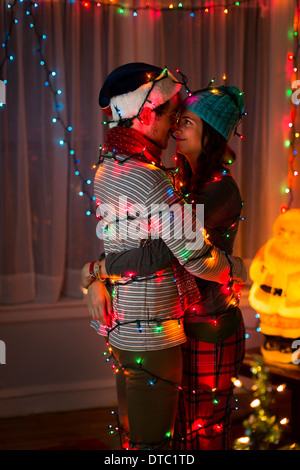 Romantic young couple wrapped in fairy lights at christmas - Stock Photo