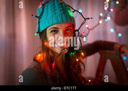 Portrait of young woman wrapped in christmas lights - Stock Photo