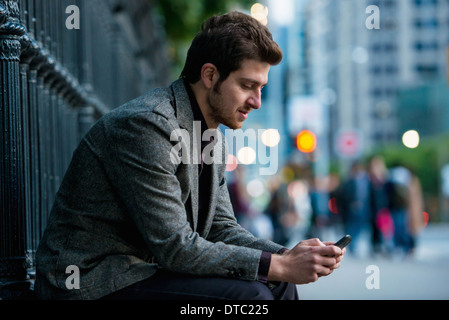 Young man waiting on city street, Toronto, Ontario, Canada - Stock Photo