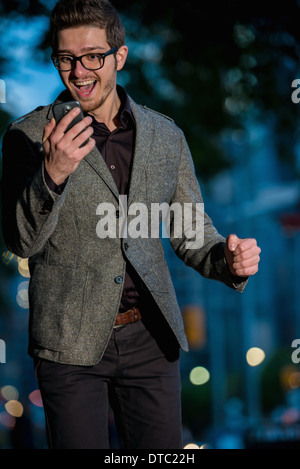 Excited young man looking at mobile phone, Toronto, Ontario, Canada - Stock Photo