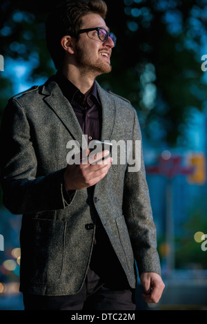 Young man strolling down street with mobile phone, Toronto, Ontario, Canada - Stock Photo