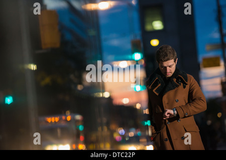 Young man waiting on street looking at watch, Toronto, Ontario, Canada - Stock Photo