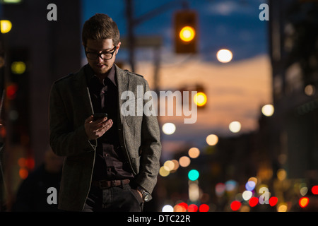 Young man strolling down street looking at mobile phone, Toronto, Ontario, Canada - Stock Photo