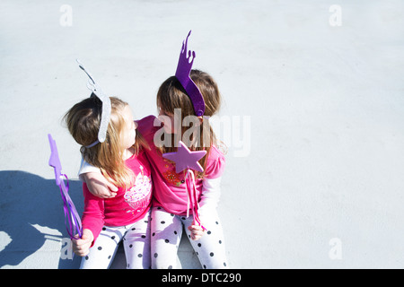 Two young sisters dressed up as fairies holding wands - Stock Photo