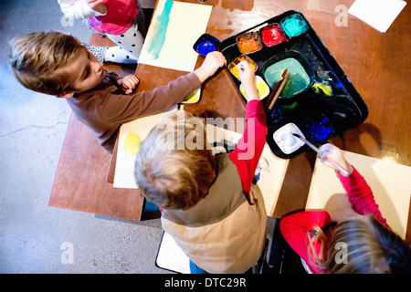 Four young siblings painting pictures at table - Stock Photo