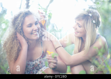 Two teenage girls with wildflowers in woodland - Stock Photo