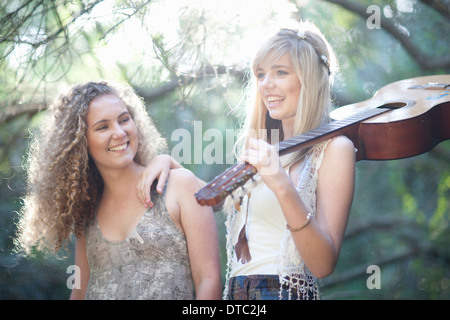 Two teenage girls with acoustic guitar in woodland - Stock Photo