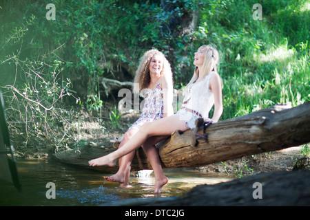 Two teenage girls sitting on tree in woodland stream