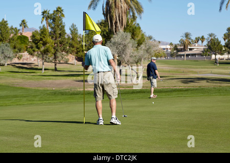 Two male golfers on the green with flag - Stock Photo