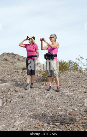 Two senior female hikers looking and photographing view - Stock Photo
