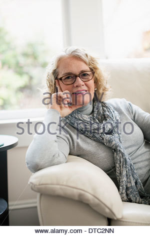 Portrait of happy senior woman sitting on sofa - Stock Photo