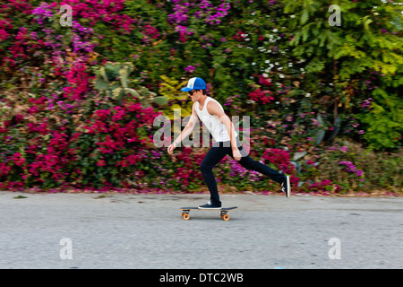 Young man skateboarding along suburban sidewalk - Stock Photo