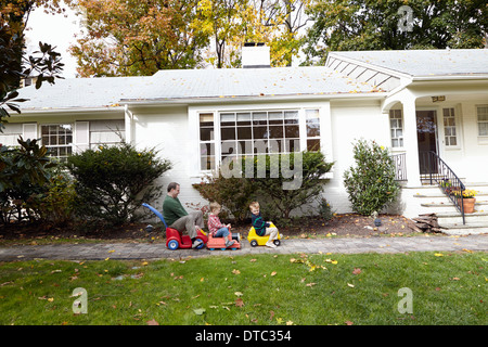 Father and young sons riding on toy cars in garden - Stock Photo