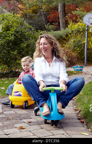 Mother and young son riding on toy cars in garden - Stock Photo