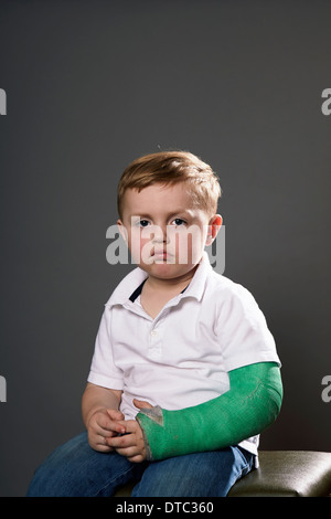 Portrait of sullen young boy with plaster cast on arm - Stock Photo