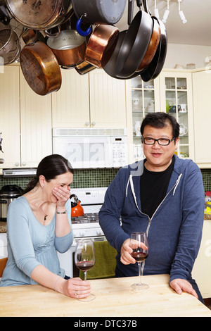 Mature couple relaxing with a glass of wine in kitchen - Stock Photo
