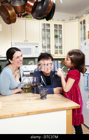 Mature couple and young daughter in kitchen - Stock Photo