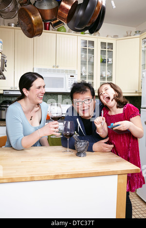 Mature couple in kitchen laughing with young daughter - Stock Photo