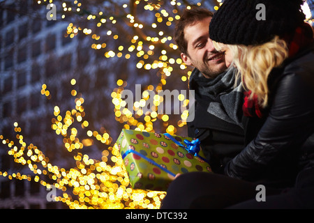 Young couple exchanging gifts next to outdoor xmas lights - Stock Photo