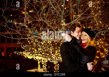 Young couple taking self portrait with city xmas lights - Stock Photo