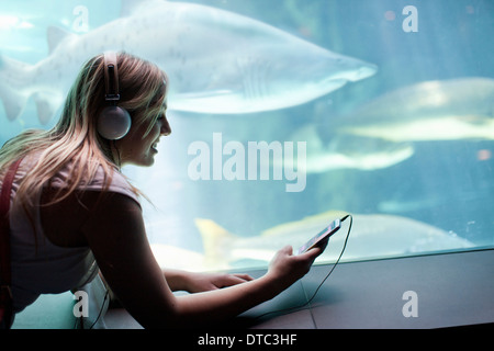 Young woman listening to music on headphones in aquarium - Stock Photo
