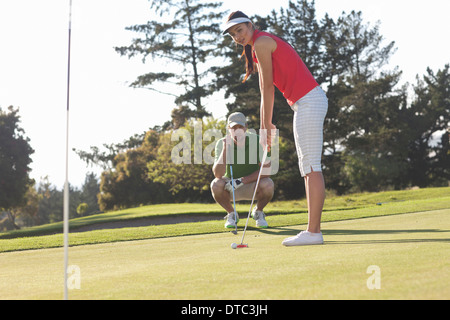 Young female golfer on golf course with trainer - Stock Photo