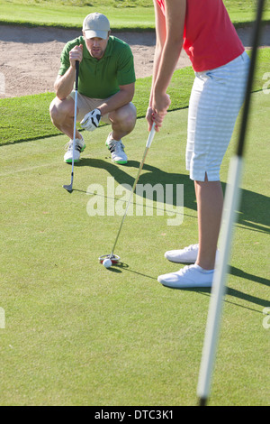 Young female lining up golf ball with trainer - Stock Photo