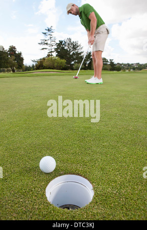 Young male golfer playing the ball on the green - Stock Photo