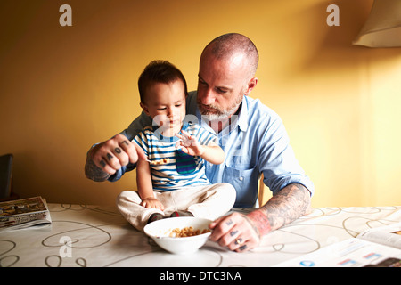 Baby boy sitting on table having cereal with father - Stock Photo