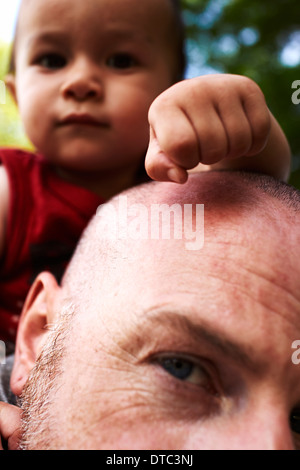 Close up of father carrying baby son on shoulders - Stock Photo