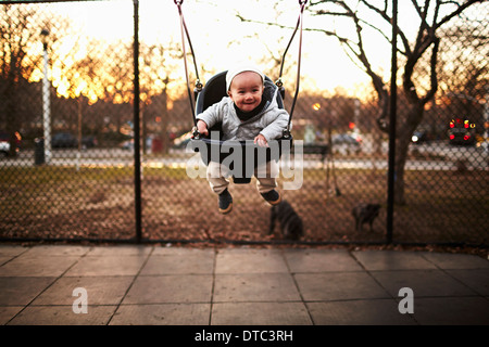 Baby boy sitting on swing in park - Stock Photo