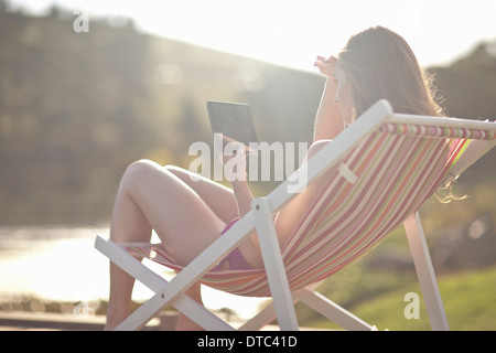 Young woman on deckchair using digital tablet - Stock Photo