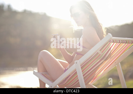 Young woman on deckchair texting from cellphone - Stock Photo