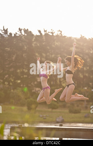 Two young women jumping off river pier - Stock Photo