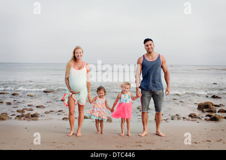 Parents and two young girls strolling on beach - Stock Photo
