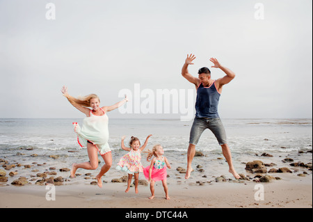 Parents and two young girls jumping mid air on beach - Stock Photo