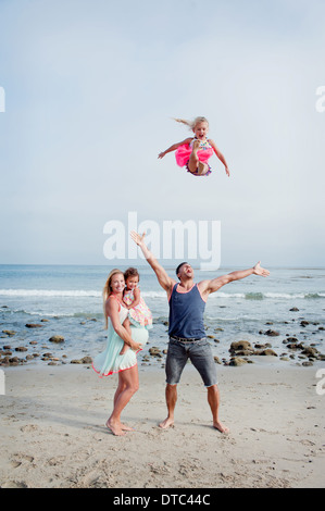 Parents and two young girls fooling around on beach - Stock Photo