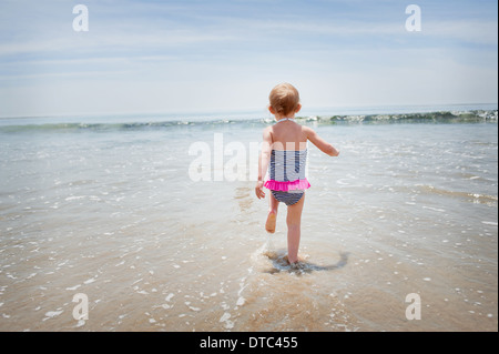 Female toddler running into the sea - Stock Photo