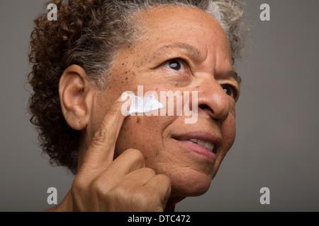 Close up studio portrait of senior woman applying face cream - Stock Photo