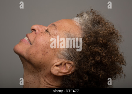 Close up studio portrait of senior woman with head back and eyes closed - Stock Photo