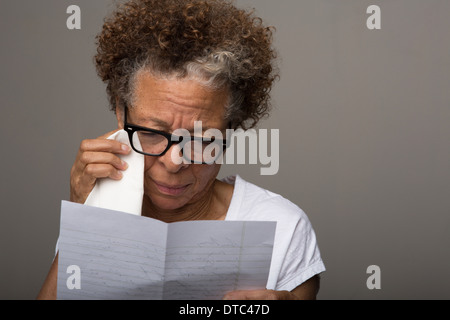 Studio portrait of sad senior woman reading a letter
