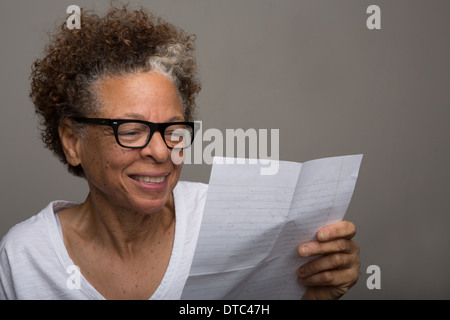 Studio portrait of happy senior woman reading a letter - Stock Photo