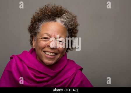 Studio portrait of happy senior woman in pink shawl - Stock Photo