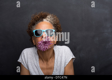 Studio portrait of senior woman with flower in her mouth - Stock Photo