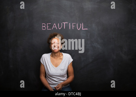 Senior woman in front of blackboard and the word beautiful - Stock Photo
