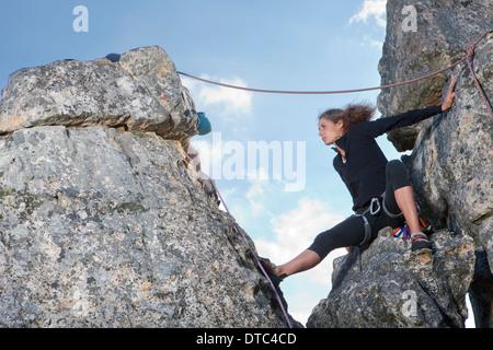 Young female rock climber sitting on rock ledge - Stock Photo