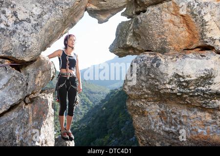 Young female rock climber taking a break on rock ledge - Stock Photo