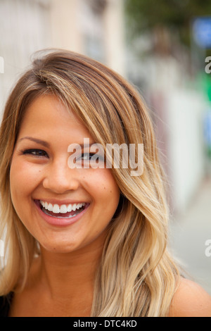 Portrait of young woman with blonde hair smiling - Stock Photo