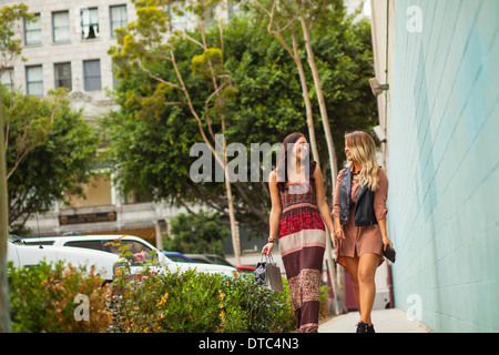 Young women walking along pavement - Stock Photo