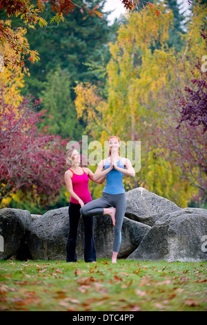 Yoga instructor teaching young woman in forest - Stock Photo